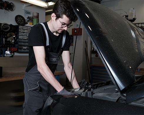 Ein Mechaniker, der bei geöffneter Motorhaube den Innenraum des Fahrzeuges checkt