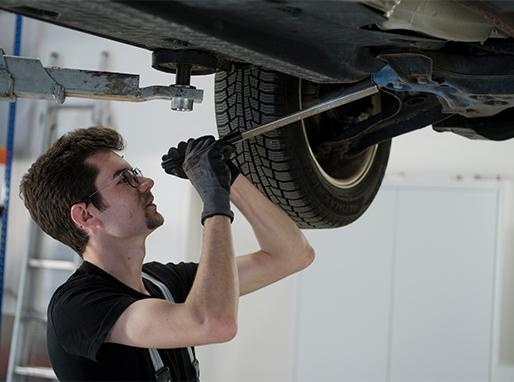Detailaufnahme von den Händen eines Mechanikers, der gerade etwas am Motor eines Fahrzeuges repariert.